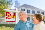 senior-couple-in-front-of-sold-real-estate-sign-house
